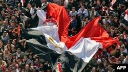 Những người ủng hộ dân chủ reo hò và vẫy cờ Ai Cập trong các buổi lễ kỷ niệm gồm có cả phần trình diễn của một ban quân nhạc