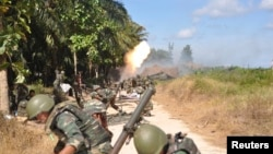 Malaysian soldiers fire toward Kampung Tanduo, where troops stormed the camp of an armed Filipino group, in Lahad Datu, Sabah state on the island of Borneo, Mar. 8, 2013 in this picture provided by Malaysia's Ministry of Defense.
