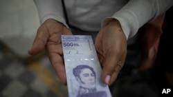 Una mujer muestra un nuevo billete de 500.000 bolívares después de retirarlo de un banco en Caracas, Venezuela, el 16 de marzo de 2021.