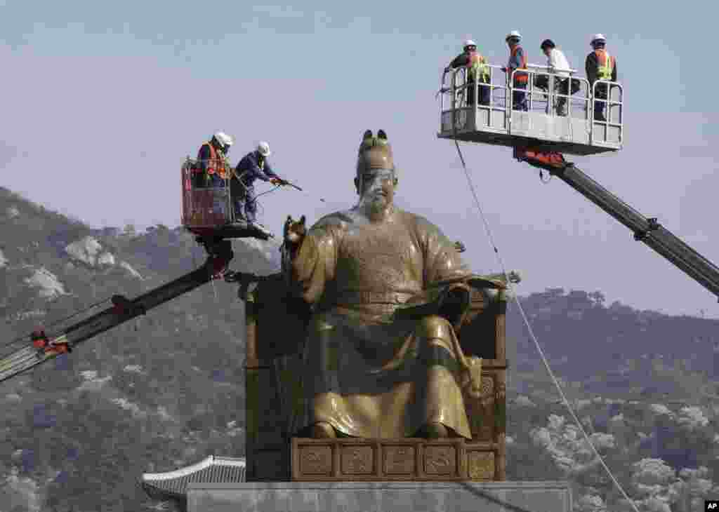 Workers clean the bronze statue of King Sejong, the fourth king of the Joseon Dynasty (1392-1910) who created the Korean alphabet, hangeul, in 1446, at Gwanghwamun Plaza in Seoul, South Korea.