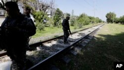 Soldados vigilan las vías del tren cerca de Guadalajara para evitar que migrantes se suban a él.