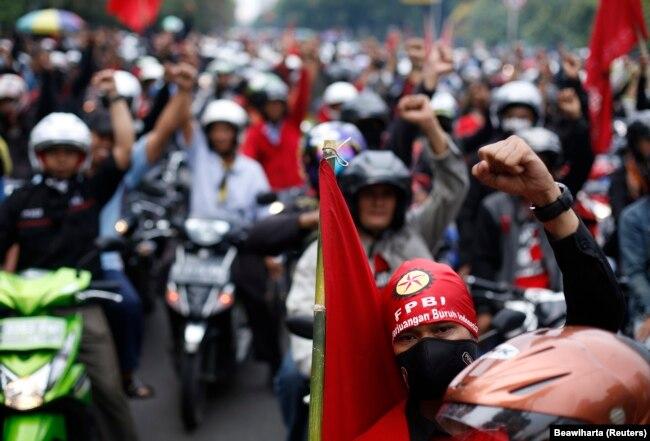 Para pekerja meneriakkan slogan-slogan saat protes menuntut kenaikan upah di Jakarta 1 November 2013. (Foto: Reuters/Beawiharta)