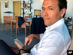 French Digital Affairs junior minister Cedric O demonstrates how to use the French app StopCovid meant to trace the virus' future spread on during an interview with the Associated Press in Paris, Friday, May 29, 2020.