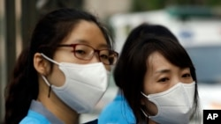 South Korean health workers wearing masks as a precaution against MERS, Middle East Respiratory Syndrome, virus, wait to check examinees' temperature and to sanitize their hands at a test site for a civil service examination in Seoul, South Korea, Saturday, June 13, 2015.