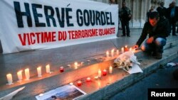 FILE - A man places a candle near a banner as people pay tribute to Herve Gourdel, a French mountain guide who was beheaded by an Algerian Islamist group, in Lyon, France, Sept. 26, 2014.