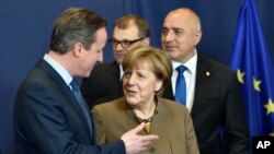 British Prime Minister David Cameron speaks with German Chancellor Angela Merkel during a photo session at a European Union summit in Brussels, Feb. 18, 2016.