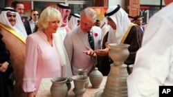 Britain's Prince Charles, center, and his wife Camilla watch a man making clay pots in a souq, or market, in Manama, Bahrain, Nov. 10, 2016.