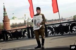共产党支持者穿着第二次世界大战时的苏联红军军服,抱着印有斯大林像的苏共喉舌《真理报》,在莫斯科的五一节集会中(2010年5月1日)