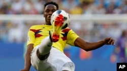 Colombia's Yerry Mina kicks during a match with Senegal in Samara, Russia, June 28. Colombia's team jersey goes for bold color. (AP)