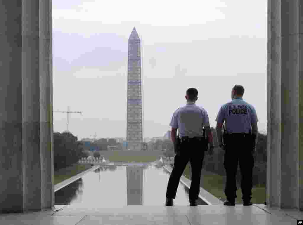 With the Washington Monument in the distance, Park Service police officers stand on duty at the Lincoln Memorial in Washington, Oct. 17, 2013.