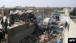 Спасатели на месте крушения самолета «Пакистан Интернэшнл Эйрлайнз» в жилом районе Карачи 22 мая 2020 года.
