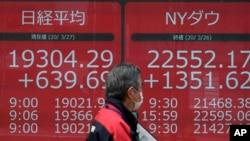 ຊາຍຜູ້ນຶ່ງ ຍ່າງຜ່ານແຜ່ນປ້າຍອີເລັກໂທຣນິກ ທີ່ສະແດງໃຫ້ເຫັນລາຄາຂອງ 225 ຮຸ້ນ ຂອງດັດຊະນີຮຸ້ນ ນິກເກອິ ຂອງຍີ່ປຸ່ນ ແລະດັດຊະນີຮຸ້ນຂອງ Dow ໃນນິວຢອກ ຢູ່ຕະຫຼາດຫຼັກຊັບຂອງໂຕກຽວ, ເມື່ອວັນສຸກ ທີ 27 ມີນາ 2020.