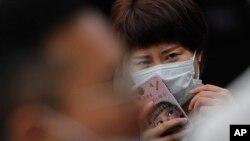 На фото: жінка у масці у Пекіні