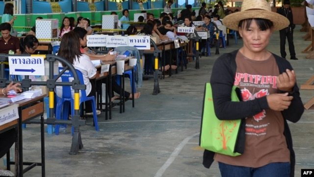 A Thai voter passes election staff at a polling station in Samut Songkhram province, south of Bangkok on March 2, 2014. Polls opened peacefully in five Thai provinces for re-runs of a widely disrupted general election.