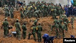 Soldiers search for survivors after a bus and two houses were buried by a mountain landslide in Altotonga in Veracruz state.