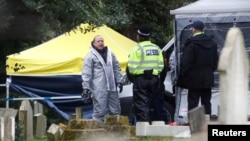 Members of the emergency services in protective suits work at the site of the grave of Liudmila Skripal, wife of former Russian intelligence officer Sergei Skripal, at London Road Cemetery, in Salisbury, Britain, March 10, 2018.