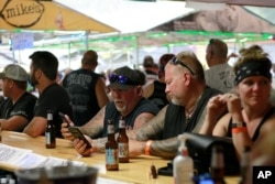 FILE - People congregate at One-Eyed Jack's Saloon during the 80th annual Sturgis Motorcycle Rally in Sturgis, S.D., Aug. 7, 2020.