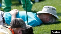 File - People nap on the 15th tee during Masters golf tournament in Augusta, Georgia, April 11, 2014.