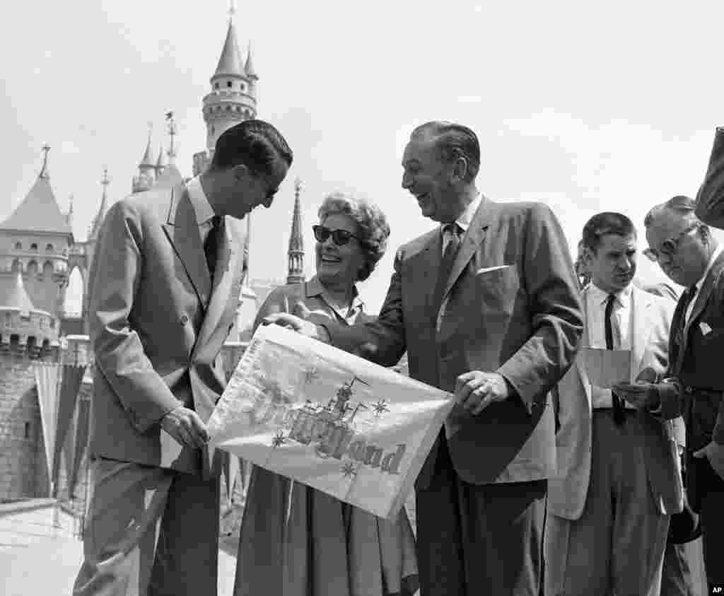 Walt Disney and his wife present King Baudouin of Belgium with a memento of his visit as they welcome him to Disneyland in Anaheim, May 20, 1959. Disney gave the visiting monarch a personally-conducted tour through the amusement park and took him on some