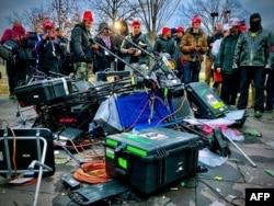 Partidarios del presidente de los Estados Unidos, Donald Trump, junto al equipo de medios que fue destruido durante una protesta frente al Capitolio en Washington, el 6 de enero de 2021.
