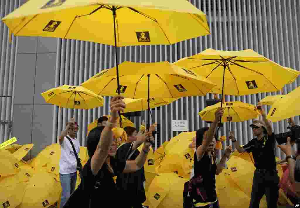 """Para demonstran mengembangkan payung kuning selama demonstrasi untuk menandai satu tahun peringatan """"Umbrella Movement"""" di luar kantor pusat pemerintahan di Hong Kong (28/9). (AP/Vincent Yu)"""
