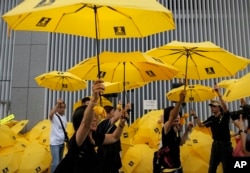 "Protesters raise yellow umbrellas during a rally to mark the one year anniversary of ""Umbrella Movement"" outside the government headquarters in Hong Kong, Sept. 28, 2015."