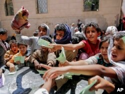 Yemenis present documents in order to receive food rations provided by a local charity, in Sanaa, Yemen.