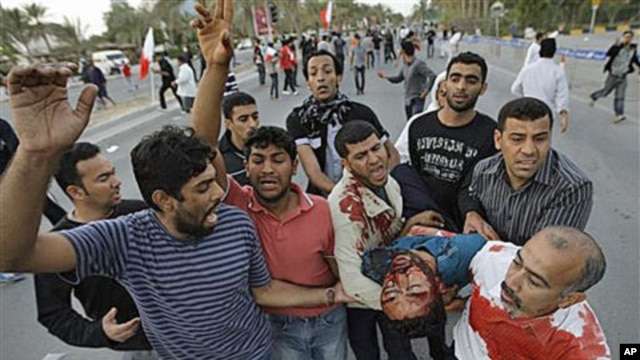 An unidentified Bahraini anti-government protestor is carried to a vehicle to be taken to a hospital after being wounded during a demonstration in Manama, Bahrain, February 18, 2011