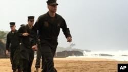 Infantes de Marina estadounidenses revisan la playa de la Bahia de Waimea, en Hawaii, como parte de las operaciones de búsqueda de dos helicópteros militares que desaparecieron el jueves 14 de enero de 2016.