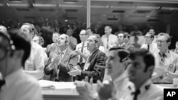 Astronaut Thomas Stafford, left, and Donald Slayton, Director of Flight Crew Operations, puff on big cigars and applaud as the Apollo 13 made a successful splashdown, April 17, 1970, Houston, Tex.