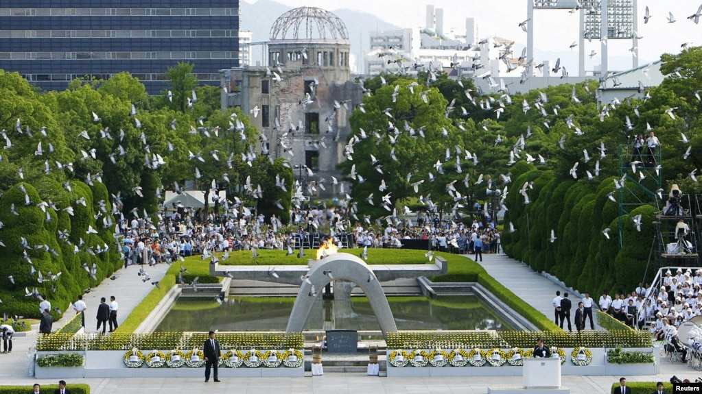 Doves Fly Over The Peace Memorial Park With A View Of Gutted Bomb