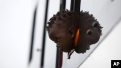FILE: A child from Zimbabwe waits for a bus to depart for Harare, from a camp for those affected by anti-immigrant violence in Chatsworth, north of Durban April 19, 2015.