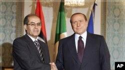 ນາຍົກລັດຖະມົນຕີອີຕາລີ ທ່ານ Silvio Berlusconi ຈັບມືກັບທ່ານ Mahmoud Jibri ຮອງປະທານສະພາ ໄລຍະຂ້າມຜ່ານແຫ່ງຊາດ ຂອງພວກກະບົດລີເບຍ ທີ່ນະຄອນມີລານ ປະເທດອີຕາລີ (25 ສິງຫາ 2011)