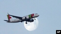 A TAP Air Portugal airplane approaches for landing in Lisbon as the moon sets, Thursday, Feb. 21, 2019. (AP Photo/Armando Franca)