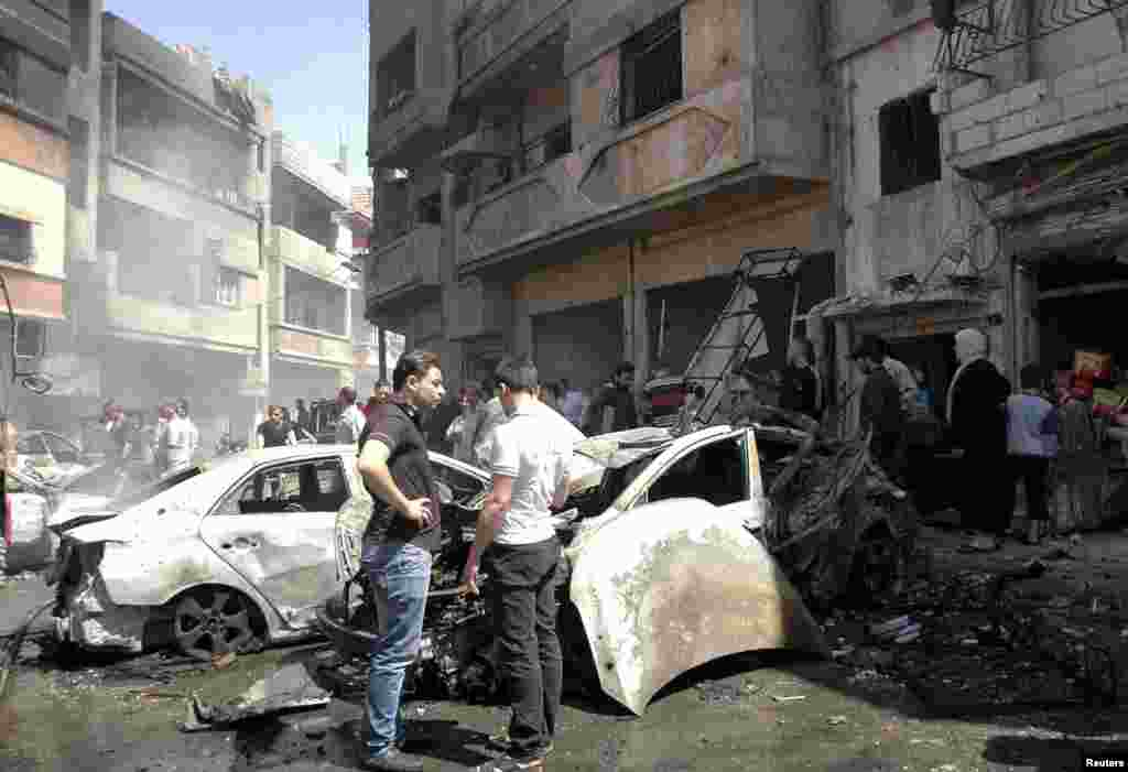 People gather at the site of two car bomb attacks at al-Abassia roundabout in Homs, April 29, 2014. (SANA)