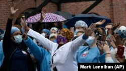 Healthcare workers react to the applause at Brooklyn's Kings County Hospital Center during the coronavirus pandemic April 24, 2020, in New York. (AP Photo/Mark Lennihan)