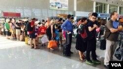 Hành khách xếp hàng lên máy bay tại sân bay Tân Sơn Nhất. (VOA/Reasey Poch)