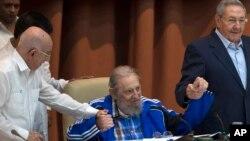 Fidel Castro akiwa amekaa na kumshika mkono kakake, rais wa Cuba Raul Castro, kulia, na naibu katibu wa pili wa chama tawala.Jose Ramon Machado Ventura,