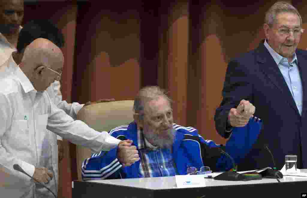 Fidel Castro sits as he clasps hands with his brother, Cuban President Raul Castro, right, and Second Secretary of the Central Committee, Jose Ramon Machado Ventura, moments before the playing of the Communist party hymn during the closing ceremonies of the 7th Congress of the Cuban Communist Party, in Havana.