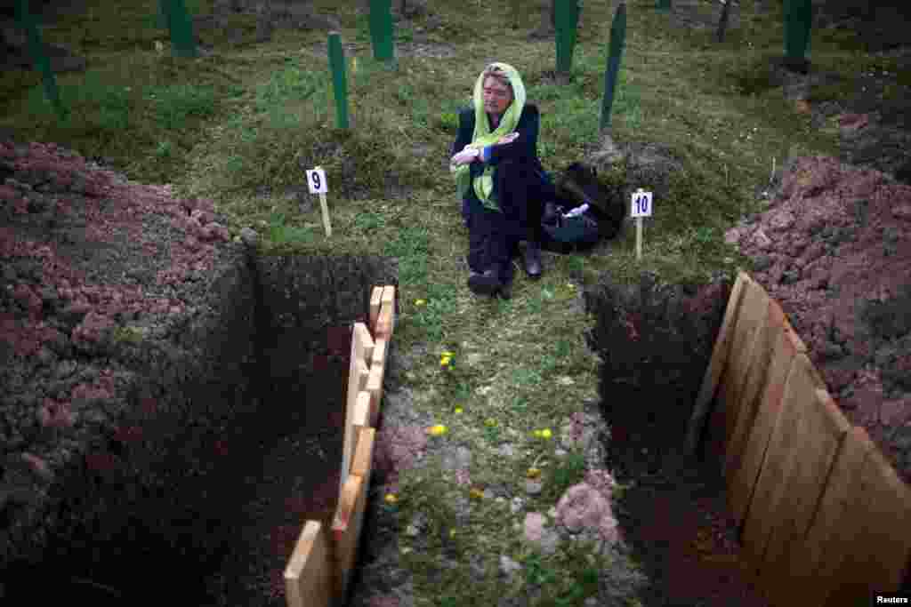 Rabija Dzodjaljevic sits and cry near graves of relatives during a mass funeral in the town of Vlasenica, in the Serbian part of Bosnia.