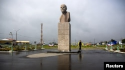 FILE - A woman walks past a statue of Soviet state founder Vladimir Lenin in Yuzhno-Kurilsk, the main settlement on the Southern Kuril island of Kunashir, Sept. 17, 2015.