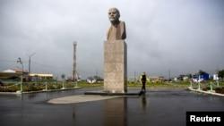 FILE - A woman walks past a statue of Soviet state founder Vladimir Lenin in Yuzhno-Kurilsk, the main settlement on the Southern Kuril island of Kunashir, Sept. 17, 2015.