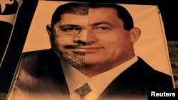 埃及示威者手持由穆爾西和穆巴拉克合成的照片抗議