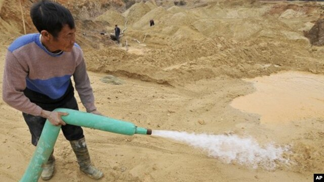 A worker waters the site of a rare earth metals mine at Nancheng county, Jiangxi province December 29, 2010.