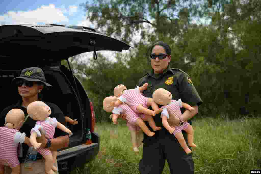 U.S. Border Patrol agents hold infant dolls in preparation for a demonstration during a 'Border Safety Initiative' media event at the U.S.-Mexico border in Mission, Texas, July 1, 2019.