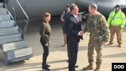 FILE - U.S. Defense Secretary Ash Carter greets Army Lt. Gen. Sean MacFarland after arriving in Baghdad, Dec. 16, 2015. Carter is on a weeklong trip to the Middle East.