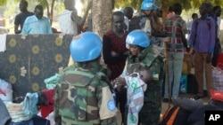 联合国南苏丹维和使团发布的照片:2016年7月14日,维和部队军人怀抱一婴孩;南苏丹人在朱巴的联合国营地寻求保护。