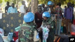 FILE - In this photo taken July 14, 2016 and released by the United Nations Mission in South Sudan (UNMISS), UN peacekeeper soldiers hold a baby as South Sudanese people seek protection at the UN camp in Juba, South Sudan.