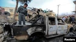 Seorang polisi Afghanistan memeriksa kendaraan yang hancur akibat serangan bom bunuh diri di gerbang markas polisi di wilayah Sarobi, sebelah timur Kabul, Afghanistan (21/2).