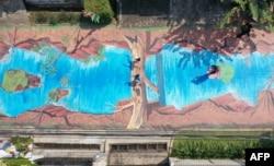 Foto udara ini memperlihatkan seorang perempuan (kanan) sedang memotret anak-anaknya (tengah) pada lukisan tiga dimensi sepanjang 300 meter, karya enam belas seniman dari Komunitas Perupa Jakarta yang melambangkan ekspresi dan semangat seniman di tengah pandemi COVID-19 di luar museum Basoeki Abdullah di Jakarta, 27 Agustus 2020. (ADEK BERRY / AFP)